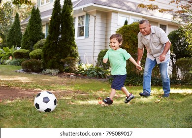 Grandfather Playing Soccer In Garden With Grandson