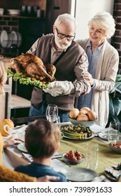 grandfather putting turkey on thanksgiving table for holiday dinner