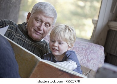 Grandfather reading a book to his grandchild