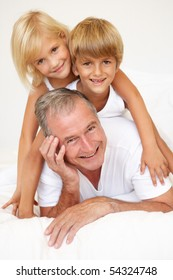 Grandfather Relaxing On Bed With Grandson