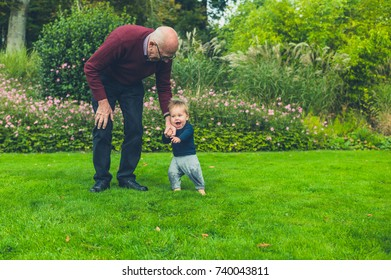 A grandfather is running and playing with his grandson on a green lawn