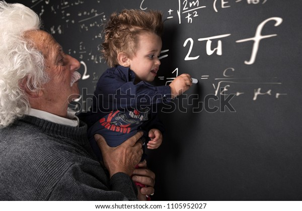 Grandfather scientist with grandchild in arm writing at the blackboard