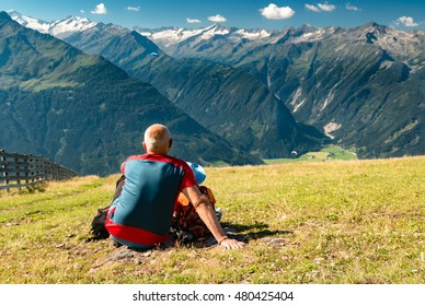 grandfather senior with little boy sitting a watching paraglides in austrian alps with high mountains peaks view