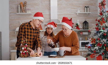Grandfather serving child with baked delicious cookie while grandmother putting coffee enjoying spending together christmastime season. Family standing in decorated kitchen during christmas holiday