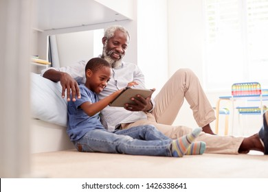 Grandfather Sitting With Grandson In Childs Bedroom Using Digital Tablet Together