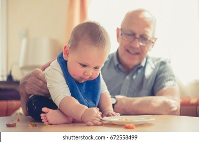 A grandfather is sitting at a table and is helping his baby grandchild learn how to eat solids