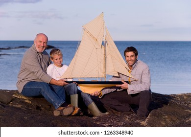 Grandfather with son and grandson holding model sailboat by sea