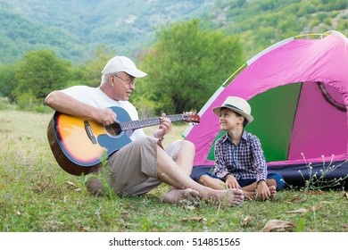 Grandfather and son playing the guitar outdoors