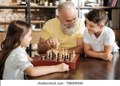 Grandfather suggesting his grandson next chess move