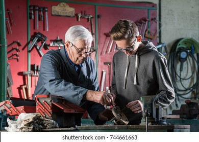 A grandfather teaches his grandchild how to tinker. They are in the grandfather's workshop, in the background there are tools hanging on the wall.