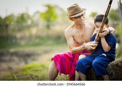 Grandfather teaches traditional music to his grandchildren, cute boy wearing thai dress holding Lao reed mouthorgan in hand at the county side of thailand,Thai culture lifestyle concept.