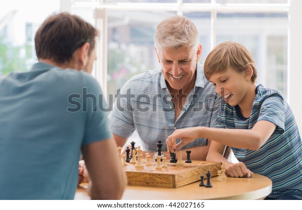 Grandfather teaching grandson how to play chess. Father and son playing chess with grandchild. Grandfather watching son and grandson playing board game at home.