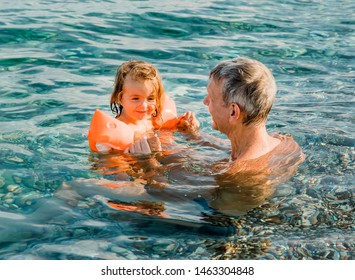 Grandfather and toddler girl having fun in sea - Cirali, Antalya Province, Turkey