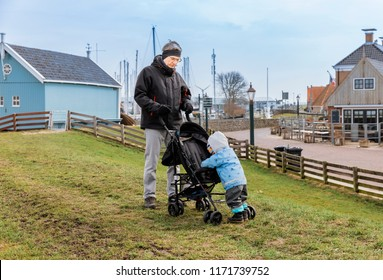 Grandfather with toddler girl on dyke – Hindeloopen, Netherlands, Europe