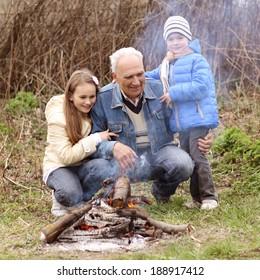 Grandfather with two grandchildren sitting around the campfire. Grandfather and grandchild