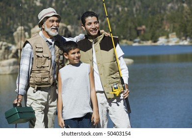 Grandfather and two grandsons holding fishing rods, standing by lake