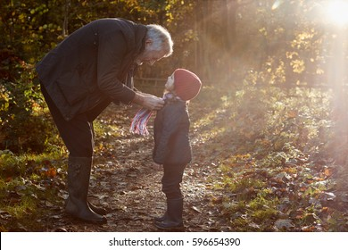 Grandfather Tying Granddaughter's Scarf On Autumn Walk