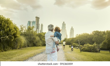 Grandfather whispering a secret to child in front of Skyline.