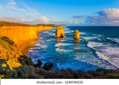 Grandiose coast of Australia. Rocks of the Twelve Apostles and powerful ocean surf at sunset. The concept of exotic, active and photo-tourism