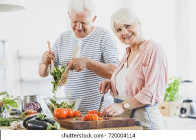 Grandma cuts pepper and grandpa mixes vegetable salad during cooking together in white kitchen