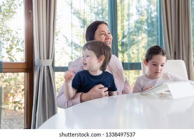 Grandma entertaining her little grandchildren with a tablet computer game