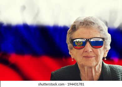 Grandma fan with national color glasses, in the background are silhouette of fans and national flag
