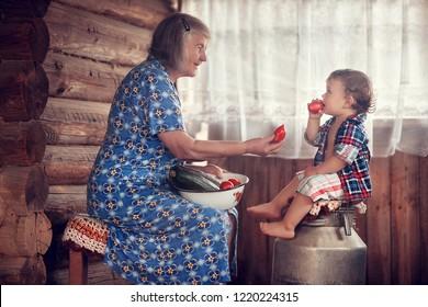 Grandma gives her grandson tomatoes