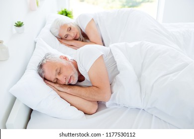 Grandma, granddad grey hair couple in pajama, sleep, wear, sleepwear, nightwear sleep on linen, sheets, big bed with their hands on their heads in bright room interior