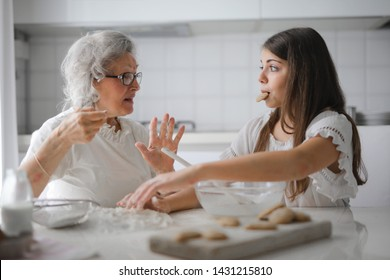 Grandma and granddaughter eating biscuit in the kitchen.