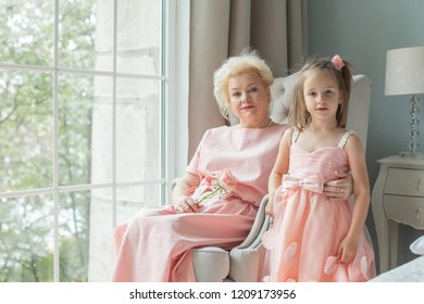 Grandma and granddaughter. Older woman and child girl at home