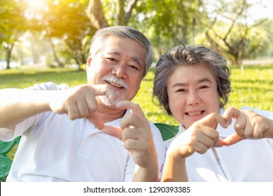 Grandma and grandpa or grandparents make symbol of love by using hands and fingers for making hearts. Lovely older couple or senior people love each other for long time. They give love to their family