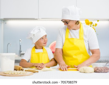 Grandma and grandson prepare food at home in the kitchen