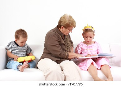 Grandma helping girl by reading and playing with baby