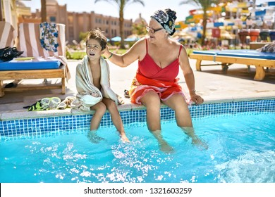 Grandma with her grandson are holding their legs in the water while sitting on the edge of the pool on the sunny background of the hotel. Lady wears a red swimsuit with headband and glasses.