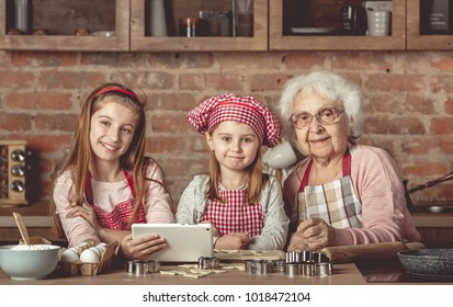 Grandma with her little granddaughters looking for a recipe using modern tablet