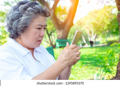 Grandma or older woman practice playing social media by using smartphone. Grandmother gets confused about high technology. Old asian woman vision is not clear lately. She get long sighted. copy space
