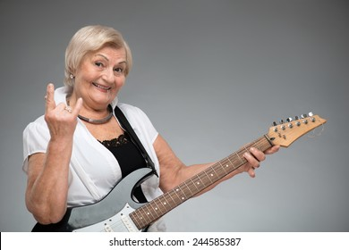 Grandma playing the guitar. Closeup of funny smiling senior woman playing the guitar and showing devils horns while standing against grey background
