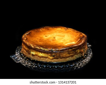 Grandma s cheesecake, freshly baked on a glass plate, black background.
