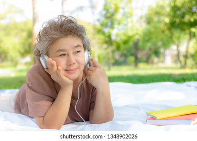 Grandma or senior woman get retired and listening music at park in summer season. Grandmother feels happy and relaxing. Old woman doesn't worry anything. Asian grandma use headphones. copy space