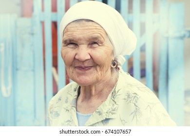 Grandma smiles near a fence, summer