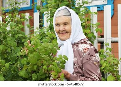 Grandma smiles near a fence, summer.