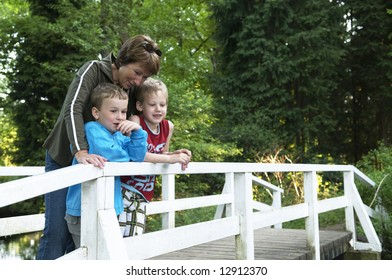 Grandma is standing on a bridge with her two grandsons, looking at a lake.