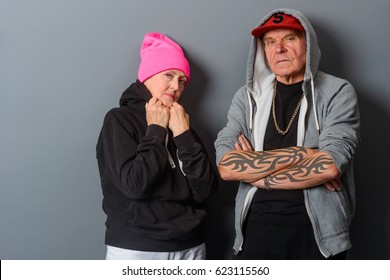 Grandma straightens her collar, grandpa's got his tattooed arms crossed. Unfriendly attitude of old gangstas. Don't mess with these pensioners.