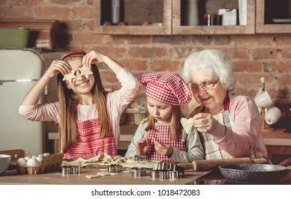 Grandma teaching granddaughters to bake homemade cookies. Little girl holding two star-shaped cookies in front of her eyes and smiling