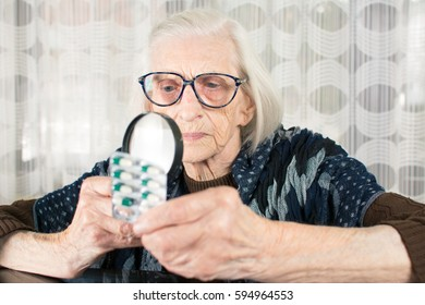 Grandma using magnifying glass to determine medicament name