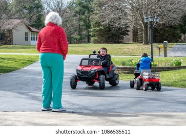 grandma watches grand kids as they ride battery operated vehicles in the drive way