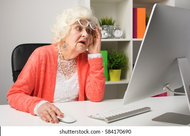 Grandma working at the office and looking at the computer in disbelief