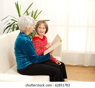 Grandmama sitting on sofa with grandchild and reading book
