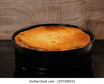 Grandma's cheesecake, freshly baked in a baking dish, against a background of wood