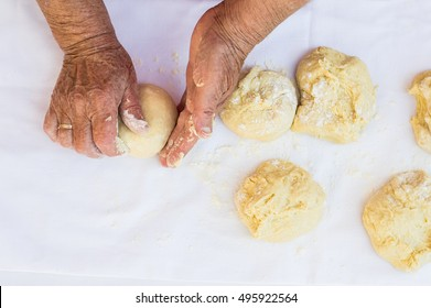 Grandma's hands knead dough on a table in her home kitchen.